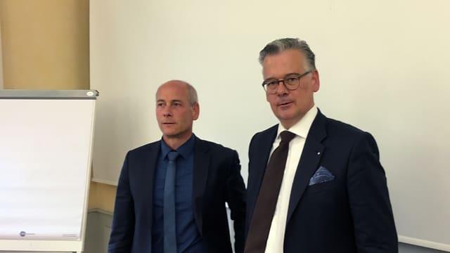 Zwei Männer blicken ernst in einem Seminarraum.