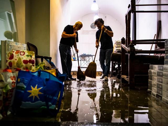 Menschen schieben mit Besen Wasser aus Wohnung.