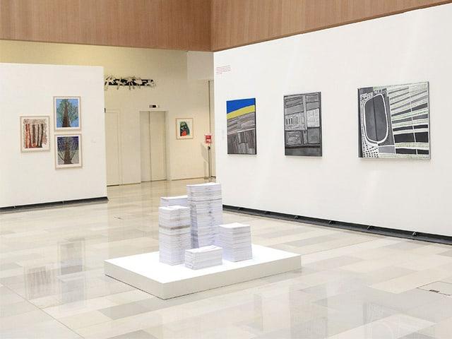 Wände mit Bildern in der Ausstellung, in der Raummitte eine weisse Skulptur.