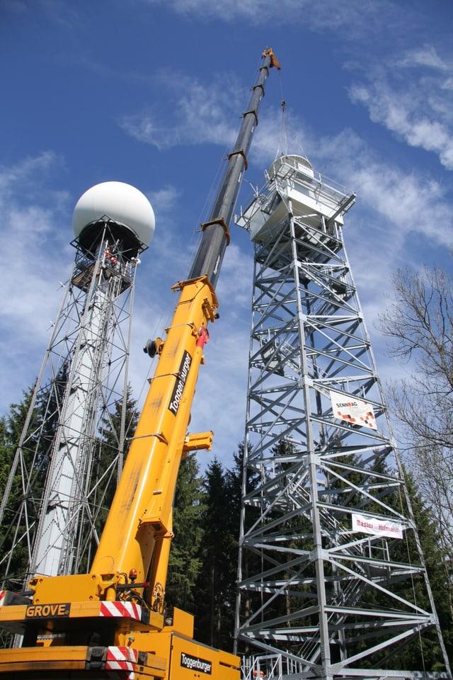 Kran stellt Radarturm auf.