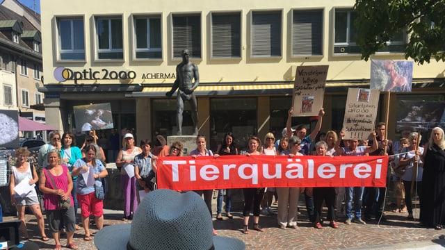 """Demonstranten mit Plakat """"Tierquälerei"""""""