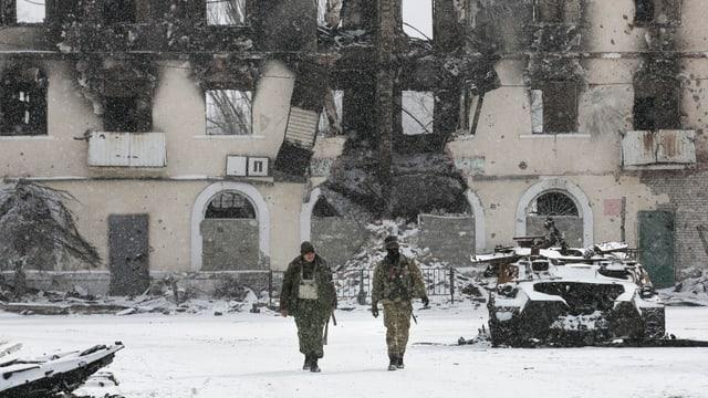Kämpfer der selbsternannten Volksrepublik Donezk laufen an einem zerstörten Transporter der ukrainischen Armee vorbei.