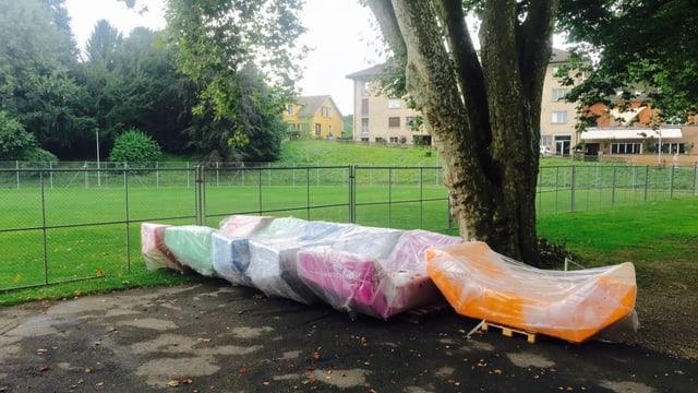 Sechs eingepackte Enzo-Möbel in verschiedenen Farben stehen auf einem Teerplatz. Dahinter sieht man Rasen.