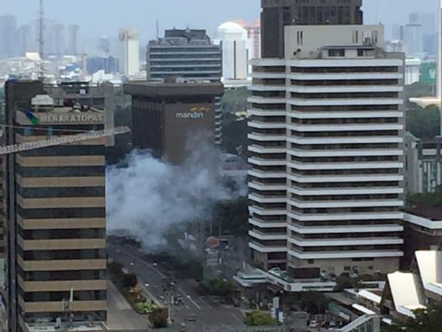 Rauch über einer Strasse zwischen Hochhäusern