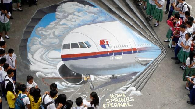 Kinder stehen um ein gemaltes Flugzeug.