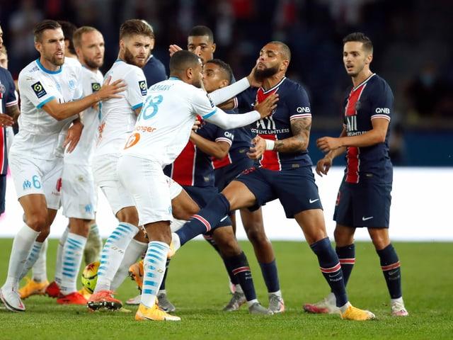 Die Spieler von Paris Saint-Germain und Marseille gehen aufeinander los.