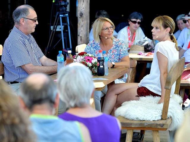 Bundesrat Guy Parmelin, Schlagersängerin Francine Jordi udn Moderatorin Sonja Hasler sitzen an einem Holztisch.
