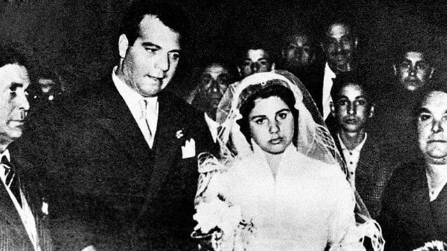 Ein junges Brautpaar, sie in klassischem Brautkleid mit Schleier (s/w).