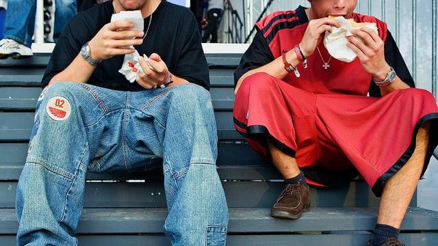 Zwei Jugendliche sitzen auf einer Treppe, in den Händen einen Kebap.