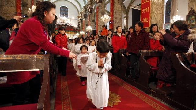Kleine Kinder als Engel verkleidet laufen den Gang einer Kirche hinunter.