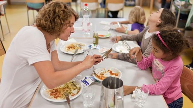 Betreuerin mit Kindern an einem Mittagstisch beim Essen
