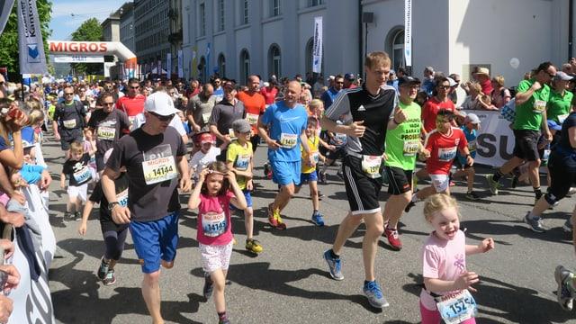 Kinder und Erwachsene springen auf der Strasse bei Sonnenschein in Sportkleidern.