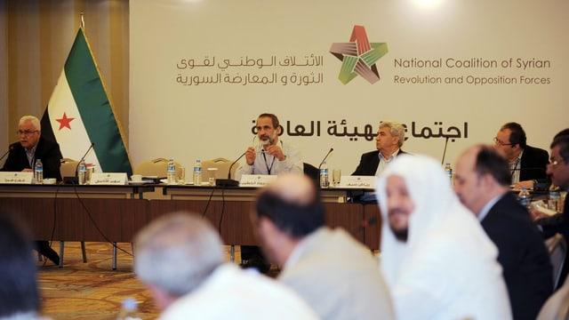 Vertreter der syrischen Opposition sitzen an einem Tisch, in der Mitte des Bildes ihr früherer Vorsitzender, Moaz Al-Kahtib.