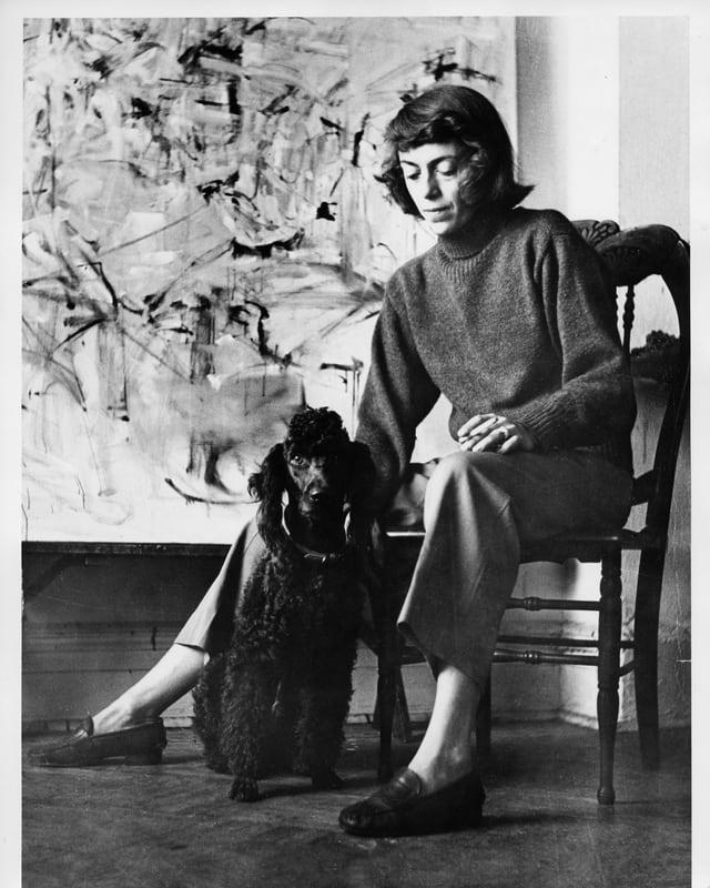 Eine Frau sitzt auf einem Stuhl und streichelt einen mittelgrossen, schwarzen Hund vor sich.