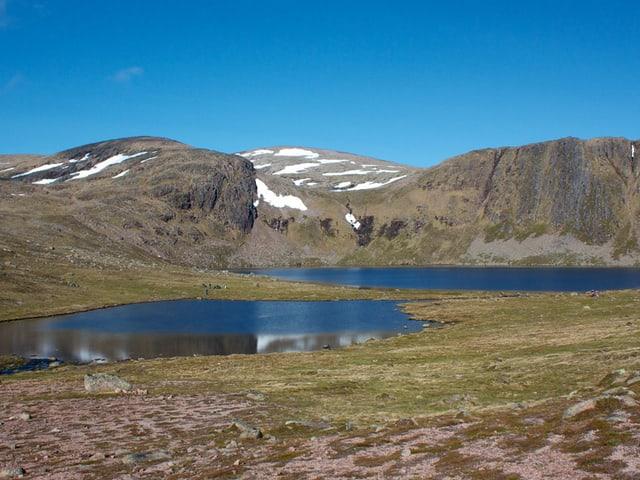 Zwei Bergseen, im Hintergrund nicht sehr hohe, aber felsige Berge mit Schneefeldern.