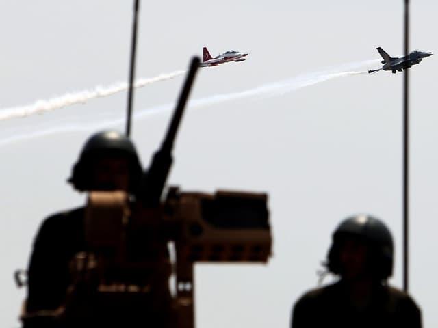 Zwei Kampfjets am Himmel. Im Vordergrund sind zwei Soldaten zu sehen.