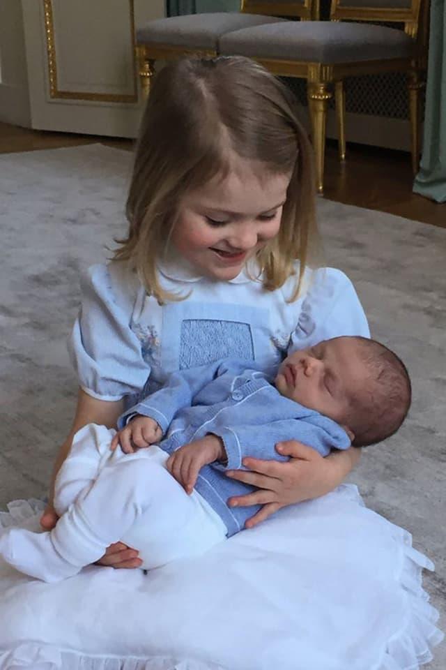 Estelle hält ein Baby in der Hand.