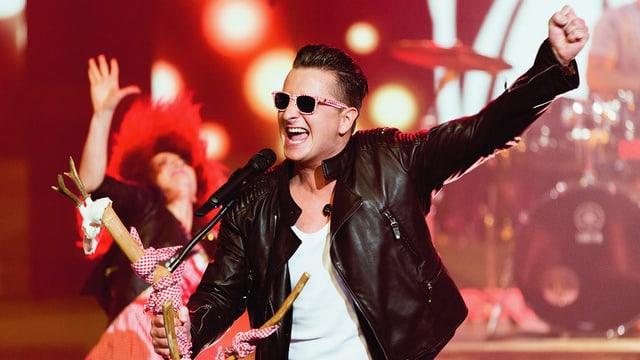 Ein Sänger in Lederjacke und mit Brille während eines Fernsehauftritts.