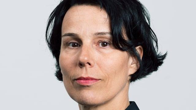 Eine Frau im schwarzen Blazer und mit schwarzem Haar.