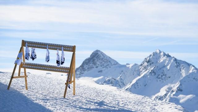 Sechs Startnummern hängen an einer Holzvorrichtung im Skigebiet.