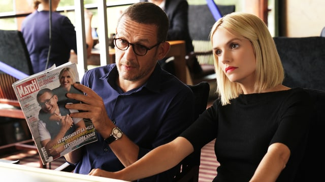 Mann mit Zeitschrift und Frau sitzen nebeneinander.