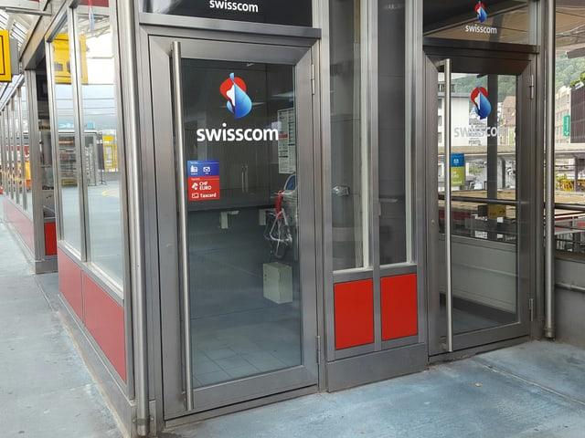 Duas gabinas da telefon cun eschs da glas cun si il logo da la Swisscom.