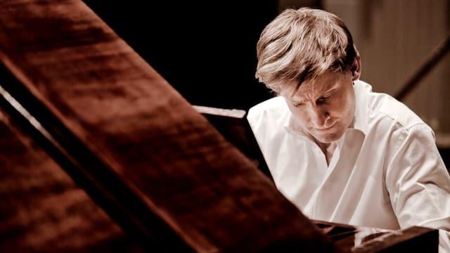 Mann sitzt an Klavier und spielt.