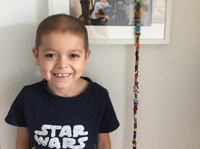Finn lächelt in die Kamera, hinter ihm an der Wand eine farbige Kordel und ein angeschnittenes Foto des Pflegeteams.