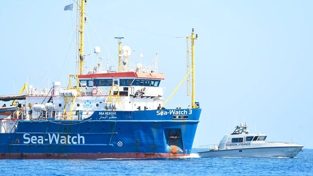 """Man sieht ein blaues Rettungsschiff, auf dem """"Sea Watch"""" geschrieben steht und ein kleineres, weisses Boot der Polizei."""