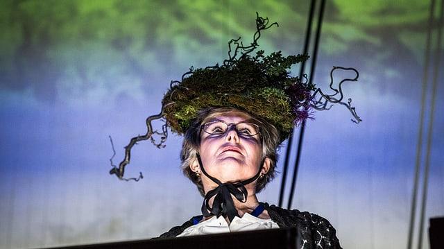 Eine Frau trägt einen Hut, der mit Wurzeln und Moos bestückt ist.