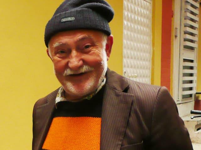 Ein älterer Mann mit Mütze und orange-schwarzem Pullover.