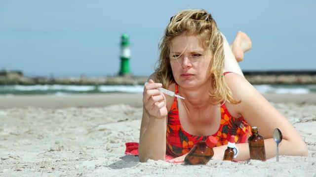 Eine Frau liegt mit Fieberthermometer in der Hand am Strand, umgeben von Medikamentenfläschchen.