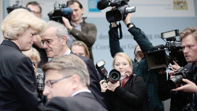 Eine Frau und zwei Männer vor Fotografen und Kameraleuten.