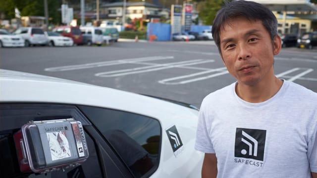 Auto mit Geigerzähler an der Scheibe, daneben ein Japaner um die vierzig mit SAFECAST T-Shirt-