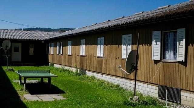 Kleine Gebäude aus braunem Holz mit weissen Läden