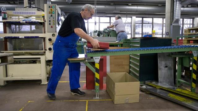 Arbeiter nimmt in einer Fabrikhalle etwas vom Rollband