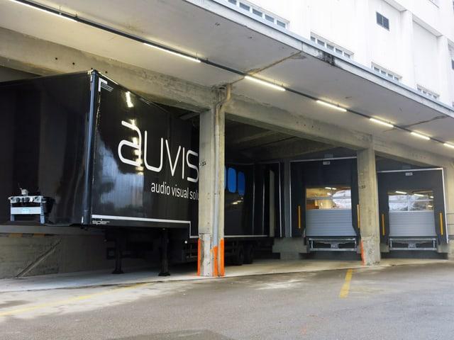 Ein schwarzer Lastwagen mit der Aufschrift «auviso» steht an einer Rampe.