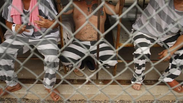 Illegale Immigranten in einem Gefängnis im US-Bundesstaat Arizona sitzen in gestreiften Uniformen hinter einem Maschendrahtzaun. (reuters)