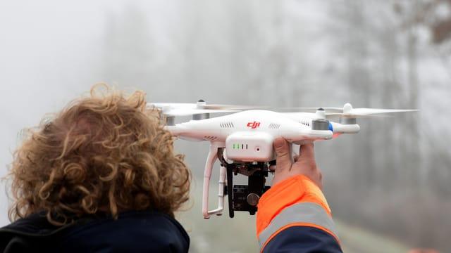 Ein Pilot hält seine Drohne in der Hand.