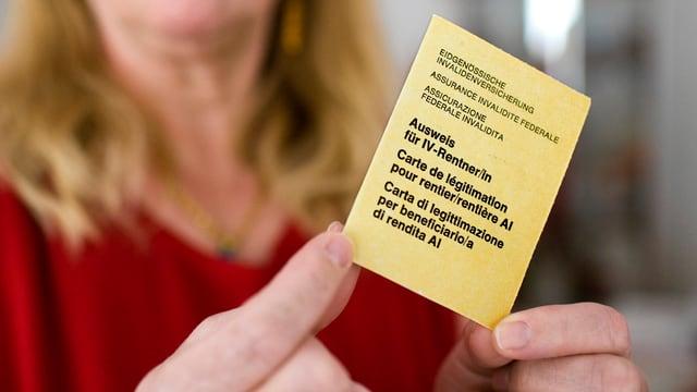 Eine Frau in rotem Kleid hält einen gelben IV-Rentnerausweis in die Kamera.