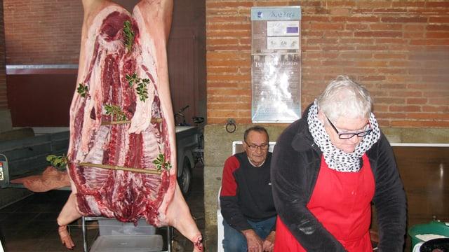 Ein Marktstand: Ein halbes Schwein hängt von der Decke, daneben steht eine Frau mit dickem Schal und roter Schürze.
