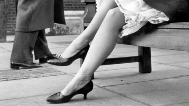 Schwarzweiss-Foto von Frauenbeinen in Strumpfhosen.