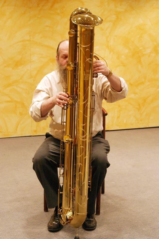 Ein Mann spielt auf einem grossen, fast mannshohen Blasinstrument.