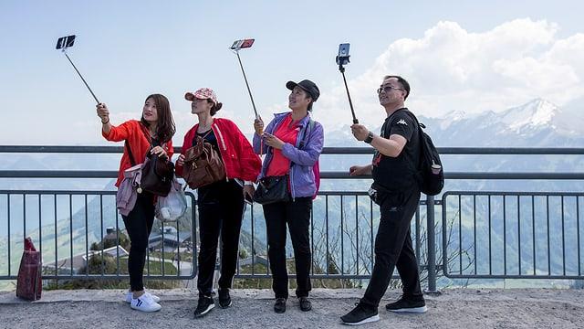 Turists da l'Asia tar selfies segirs sin il Stanserhorn.