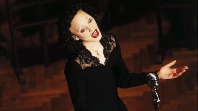 Eine stark geschminkte Frau steht vor einem Mikrofon und singt mit geschlossenen Augen.