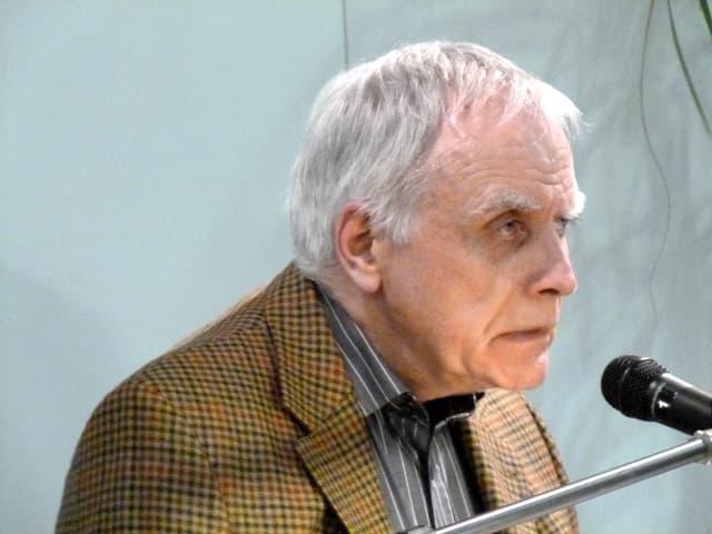 Moshe Kahn über ein Mikrofon gebeugt, vom alter gezeichnet.