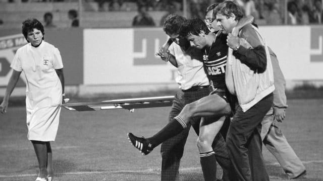 Ein verletzter Fussballspieler wird von Sanitätern vom Spielfeld gebracht