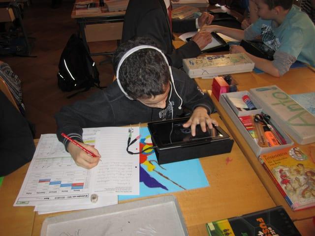 Ein Junge mit weissen Kopfhörern schreibt einen Text.