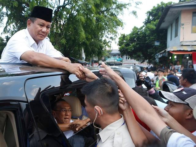 Prabowo Subianto steht im Schiebedach eines Autos und schüttelt Hände seiner Anhänger