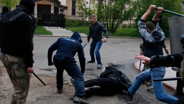 Pro-russsische Kräfte schlagen auf einen am Boden liegenden Mann ein